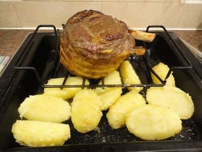 Put the parboiled potatoes into the roasting tin under the beef