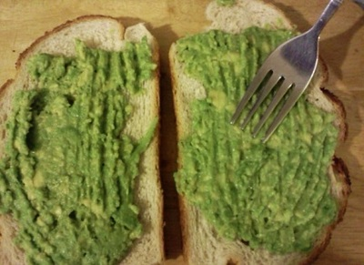 Spreading avocado paste on to bread slices