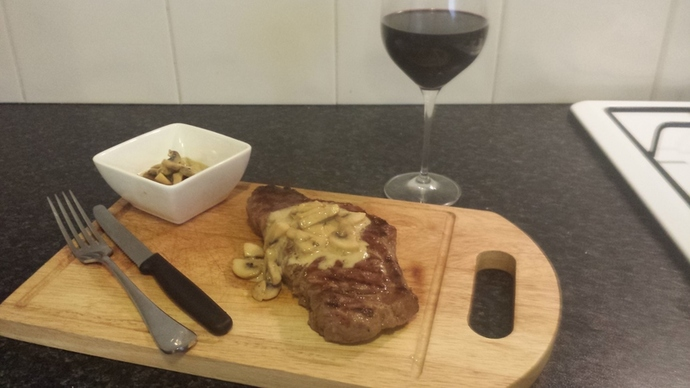 A perfectly cooked steak with chunky mushroom sauce