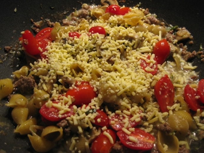 adding,cheese,tomatoes,to,mince,pasta