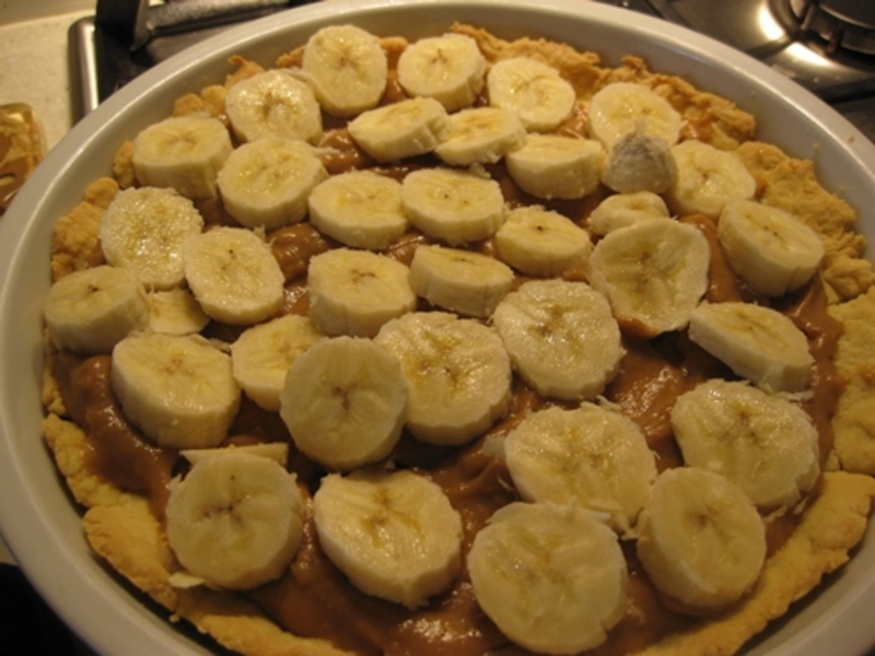 adding,sliced,bananas,to,caramel,tart