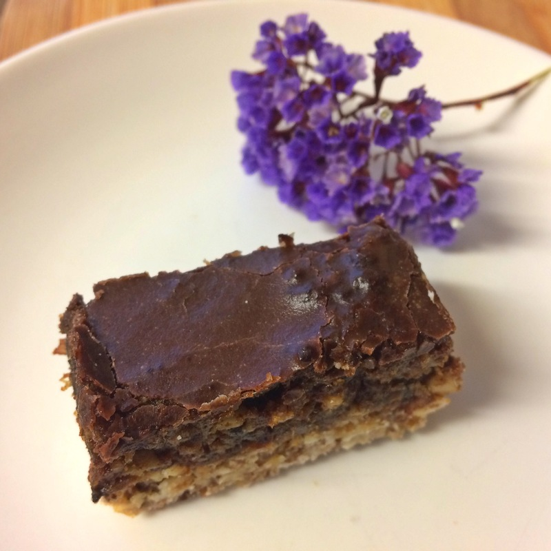Chocolate caramel fudge slice with cashews and purple flower