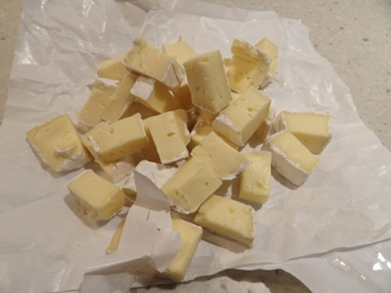 cutting,camembert,cheese,into,cubes,for,strata  - Salmon and Camembert Strata Vegetarian Pudding