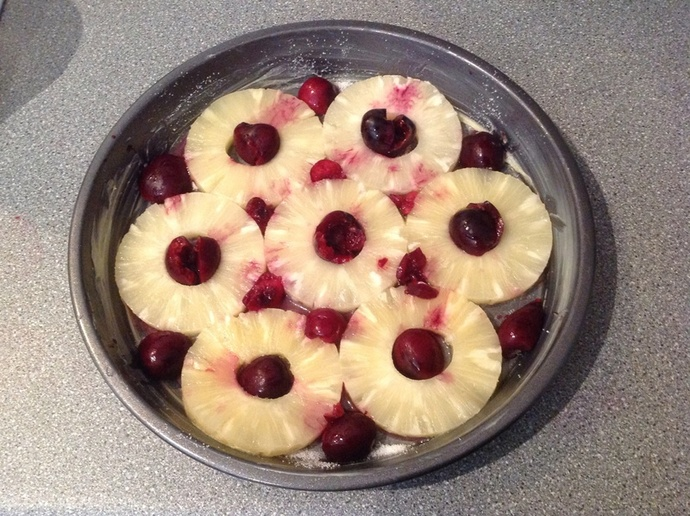 Greased baking tray, pineapple rings, cherries