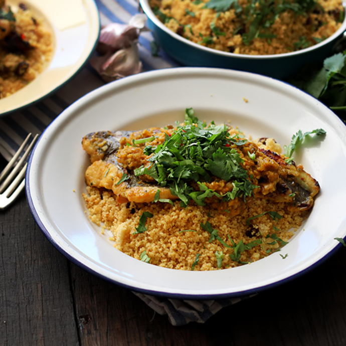 Grilled marinated fish sits on a bed of golden cous cous, garnished with coriander.