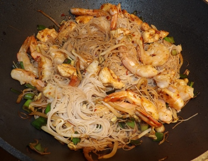 mixing,all,ingredients,in,wok,for,char,kway,teow