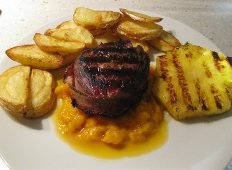 plated,steak,on,a,bed,of,mashed,mango,with,chips,and,pineapple