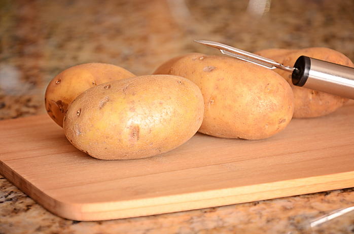 Potatoes and peeler on a cutting board