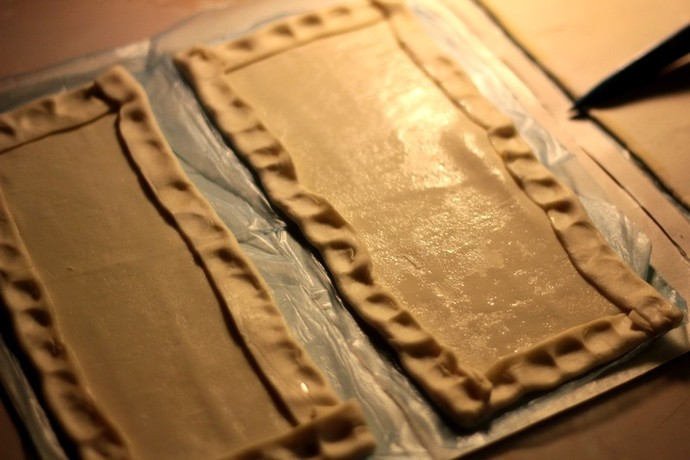 Oiling puff pastry pizzas