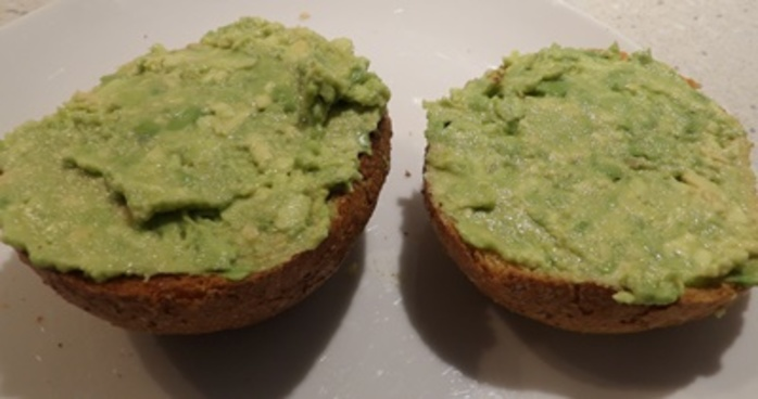 spreading,avocado,into,thick,toasted,bread