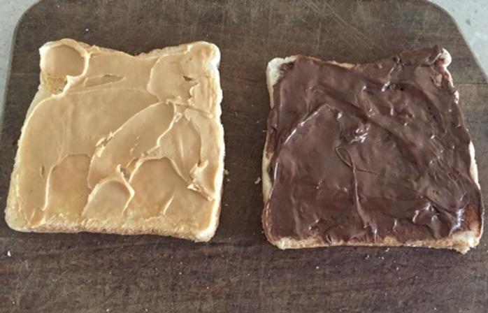 spreading,bread,with,nutella,and,peanut,butter