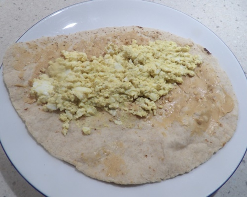 spreading,curried,egg,on,wrap  - Satay Egg and Chicken Salad Wrap