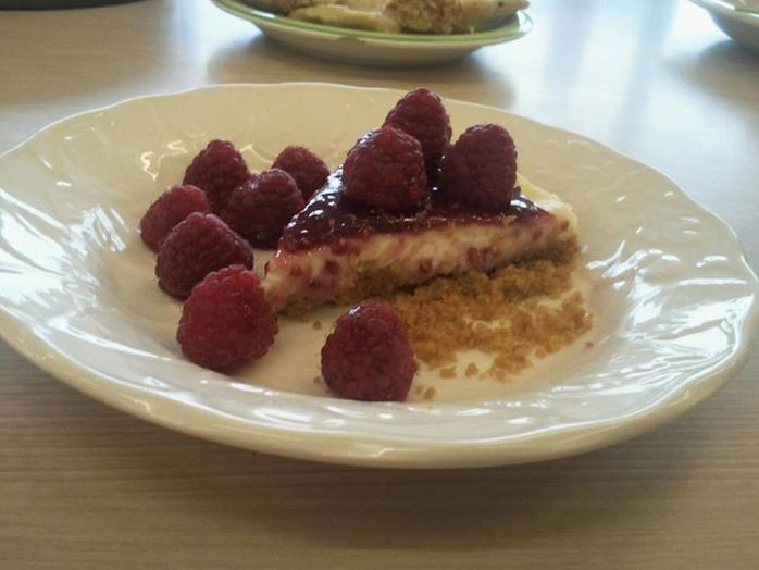 The finished dish, served with a raspberry coulis, biscuit crumb and fresh raspberries.