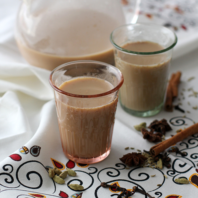 2 glasses of warm milky chai tea, sweetened with honey and aromatic with spices