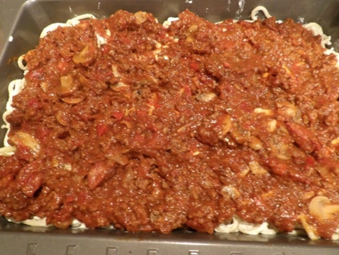 adding,mince,to,top,of,spaghetti,mixture
