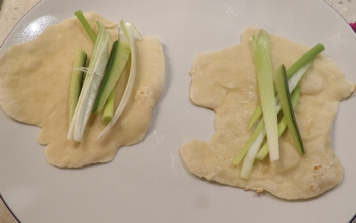 adding,spring,onions,and,cucumber,to,pancakes