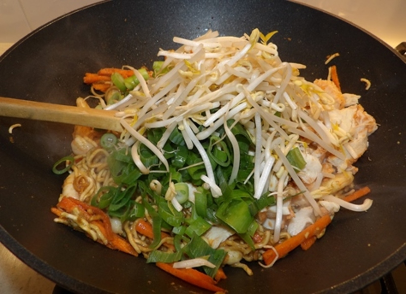 adding,spring,onions,and,shoots,to,curry,noodles  - Curry Noodles with Chicken, Prawns and Eggs