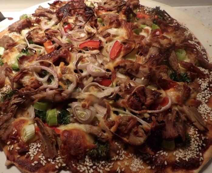 adding,final,ingredients,to,duck,pizza,with,hoisin,sauce