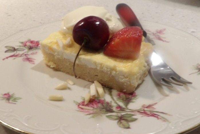 lemon,ricotta,slice,with,a,dollop,of,thickened,cream,and,strawberries