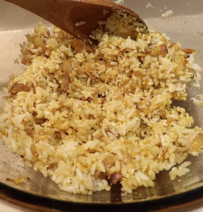 mixing,rice,onions,egg,for,base,of,corn,chicken,pie