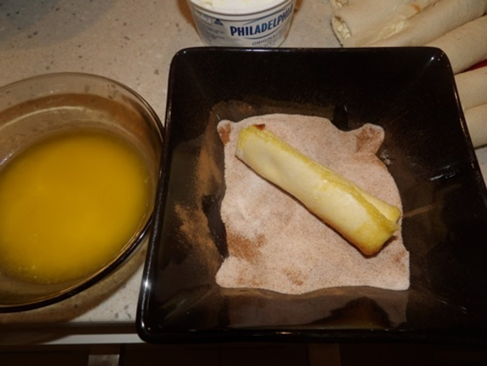 rolling,bread,in,melted,butter,and,cinnamon,sugar