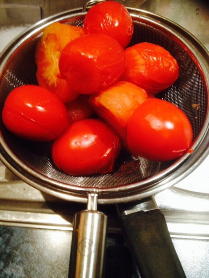 Straining tomatoes over the sink